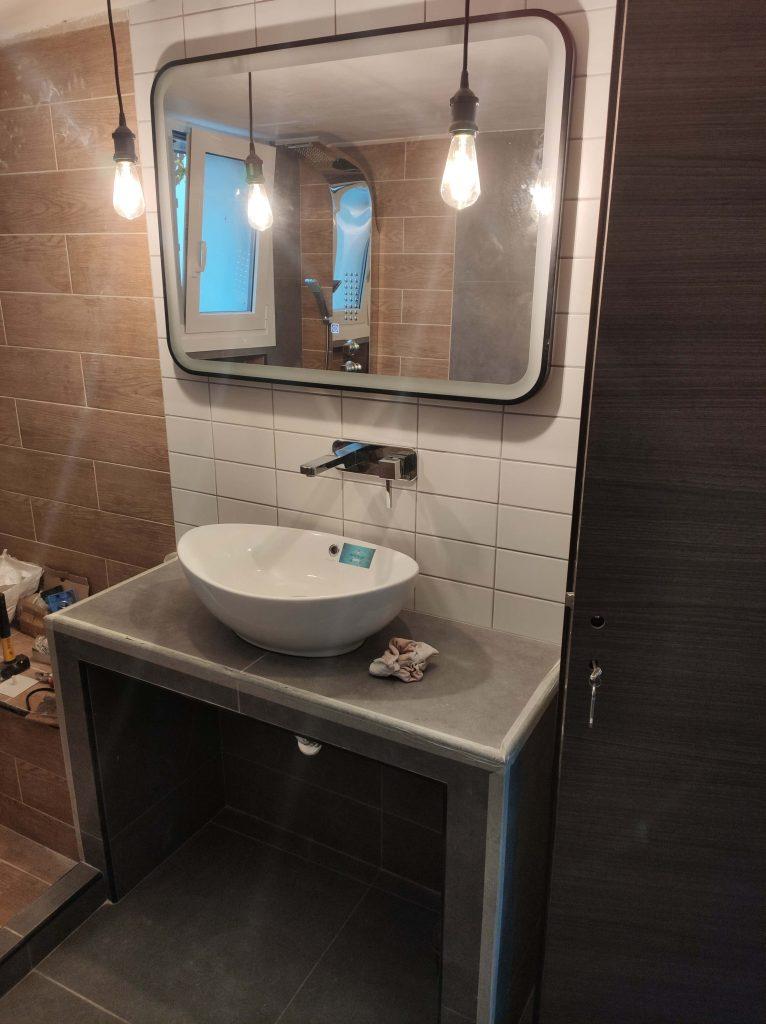 Χτιστή χειροποίητη κατασκευή νιπτήρα με εντοιχιζόμενη μπαταρία και κρεμαστά φωτιστικά σε ανακαίνιση μπάνιου Κορυδαλλός